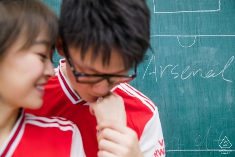 Beijing Engagement Photo Session - Portrait contains: red, shirts, couple, green, chalkboard, arsenal