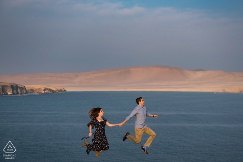 Paracas Peru Engagement Photography - Portrait contains: Couple Jumping in front of the ocean and desert