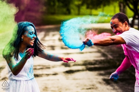 Germany Couple throwing powder on each other | Engagement Photo Session - Portrait contains:green, blue, pink, laughing, fun, together, smiles