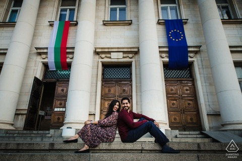 Sofia Couple Portraits - Bulgarian National Library Engagement Photography - Image contains: steps, building, back, sitting, flags, concrete, pillars