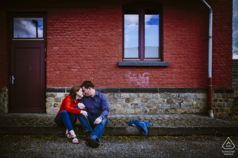 Aachen, Germany Engagement Photography - Image contains: red, brick, sitting, couple, cobblestone