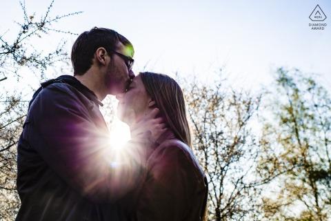 Germany Engagement Couple Portrait - Image contains:kiss, head, sun, sunlight, burst, flare