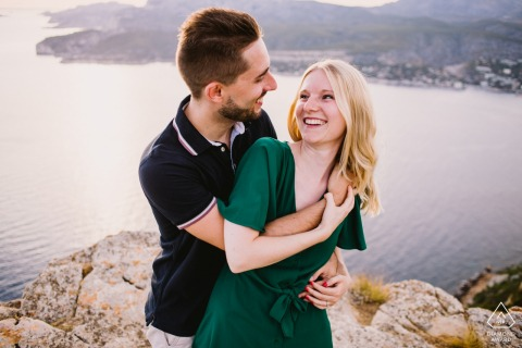 Marseille Bouches-du-Rhone Engagement Session with a couple - Portrait contains: hug, hold, laugh, smile, cliffs, water, coast, look, posing