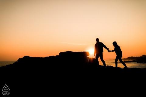 一對夫婦在日落時分在海洋上方的懸崖上的岩石上行走的剪影圖片| Depositphotos® 訂婚攝影師