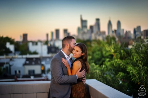 Couple shares a hug in Philadelphia. | Engagement Photography - Image contains:balcony, embrace, kiss, skyline, trees