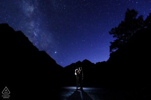 Engaged couple pose under the stars in Aspen, Colorado for a lit portrait.