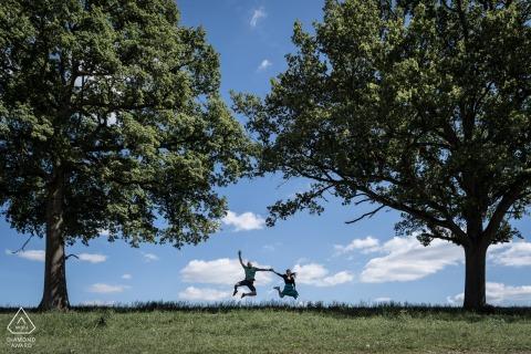 Ille et Vilaine, Frankrijk Paar portretten tijdens verlovingsactie Schiet onder twee bomen en de blauwe lucht.