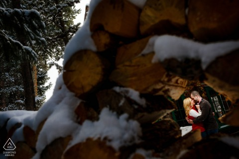 Breckenridge, CO pre wedding portraits. - Framing the couple with a stack of wood for their Breckenridge winter engagement session.