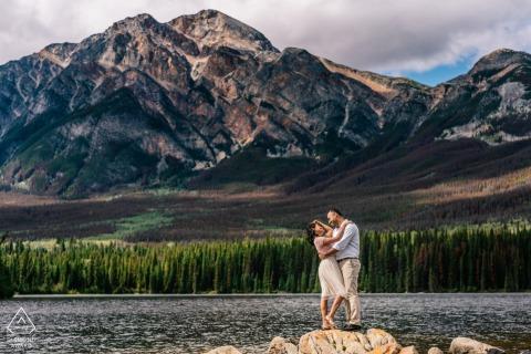 Een verloofd paar poseren samen in de bergen. Pyramid Island, Jasper National Park, AB, Canada