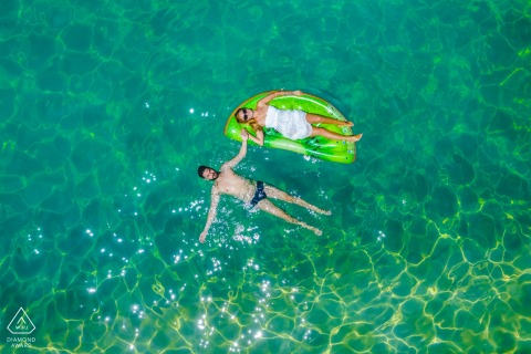 Carlentini	summer loving - engagement portrait shot with overhead drone of a couple relaxing in the water.