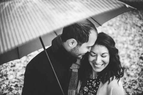 Photographie de fiançailles Attique d'un couple en train de rire sous un parapluie