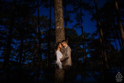 Dalat, VIETNAM Séance photo de fiançailles avec un couple au bord de la forêt avec de grands arbres.
