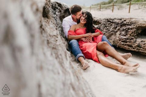 Portret in South Pointe Park, South Beach, FL-verlovingsfotosessie met een paar in het zand.