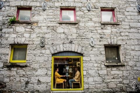 Photographie de fiançailles dans un café à Galway | Un couple assis près de la fenêtre