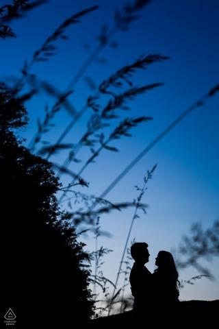 Brünner paar posiert für ein Engagement-Porträt unter dem großen blauen Himmel