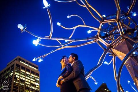 Sesión de fotos de compromiso de San Francisco - Amor en las luces de la ciudad - Una pareja se abraza bajo el arte callejero.