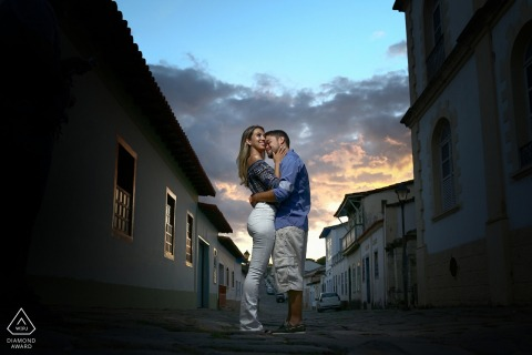 Cidade de Goiás Engagement Photo Session - Portrait contains: hug, couple, buildings, sky, sunset, alley