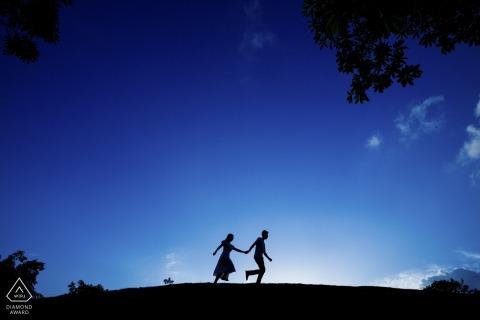Vor-Hochzeits-Verlobungs-Porträts eines Paares, das gegen den Himmel in Fujian, China läuft