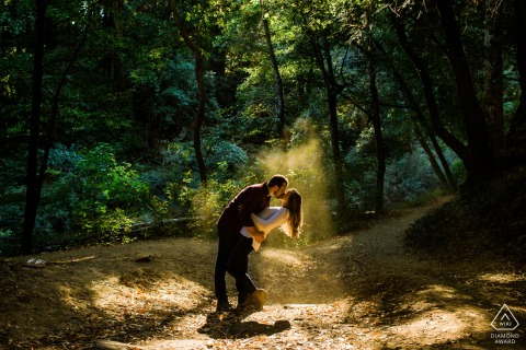 亨利·考威尔·雷德伍德斯州立公园情侣在自然光线/灰尘的口袋中接吻