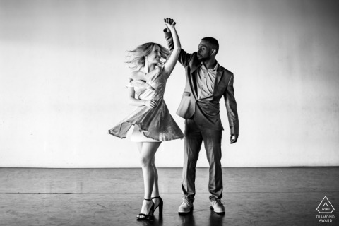 Texas - Southern Dance Studio | A couple is Dancing and spinning during an indoor engagement photo session.