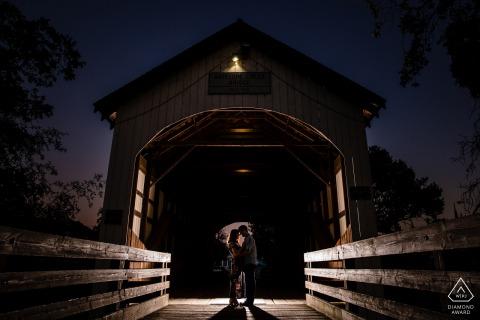 Eagle Point, Oregon Portrait de fiançailles éclairé la nuit | Un couple à l'intérieur d'un pont couvert.