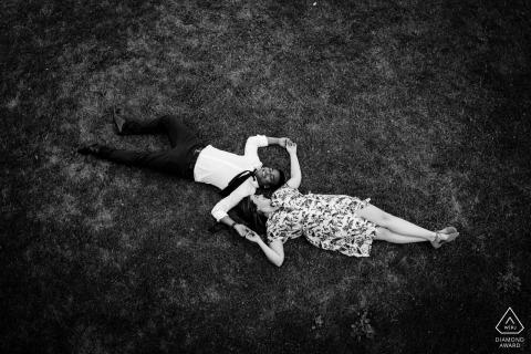 Montreal, Quebec Zwart-wit verlovingsfoto van een paar dat in het gras ligt dat vanuit vogelperspectief wordt gezien