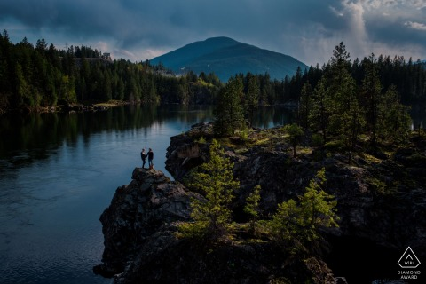 Nelson BC engagementy photography   Couple stands on rock overlooking lake