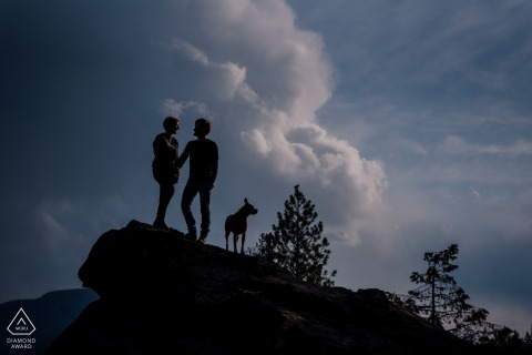 Nelson BC Couple and their dog silhouetted against the clouds during engagement photo session