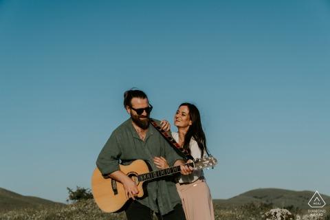 Montagnes des Abruzzes - Italie | Il joue de la guitare pour elle lors d'un shooting de fiançailles sous le ciel bleu