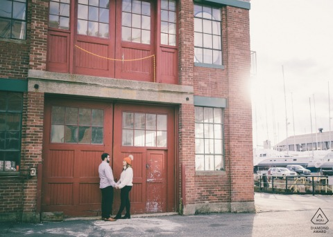 Engagement Session - The couple stands in front of the industrial-cool buildings of the East Boston Shipyard