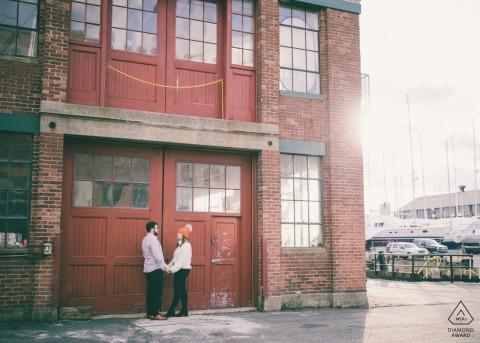Séance de fiançailles - Le couple se tient devant les bâtiments industriels de l'East Boston Shipyard