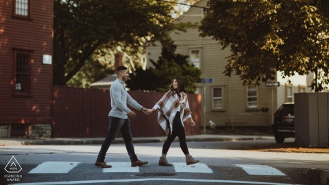 Thames Street, Newport Rhode Island séance de photographie de fiançailles avec le couple alors qu'ils traversent la rue.