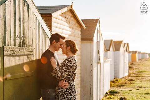 Shoreham Beach, West Sussex, UK pre-wedding portrait session | Couple embracing by the beach huts with sun flare