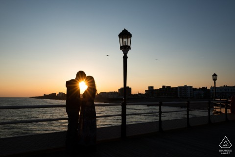 On Worthing Pier, Worthing, West Sussex, UK engagement photographer: Silhouette of couple with starburst at sunset on Worthing Pier