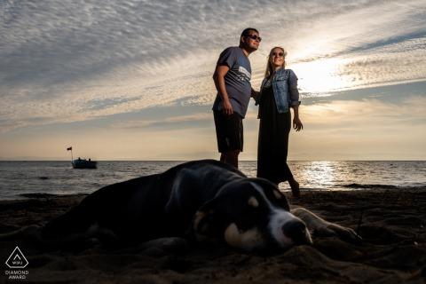 Couple is standing behind the dog at the seaside in Badavut, Ayvalık, Balıkesir