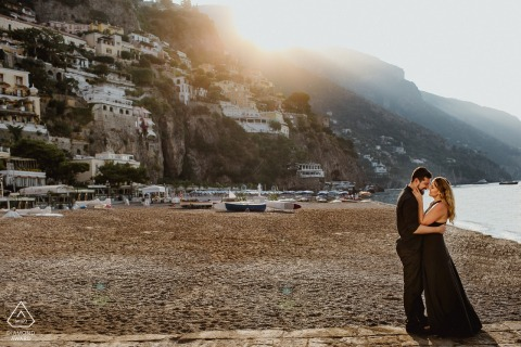 Couple at sunrise on the beach of Positano during engagement photo session.