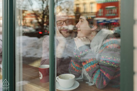 A couple snuggling in a Albany, New York cafe photographed though the window from the outside