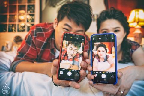 Hualien Verlobungssitzung eines Paares, das Telefone mit Bildern von sich hochhält.