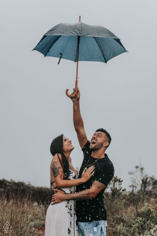Belo Horizonte, Brazil couple holding an umbrella and enjoying their engagment photo session.