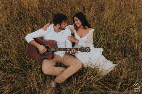 Mateus Leme engagement, prewed shoot of a couple in grasses playing a guitar.