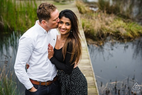 Cotswold Water Park, Cirencester, UK engagement picture session near a boardwalk over water.