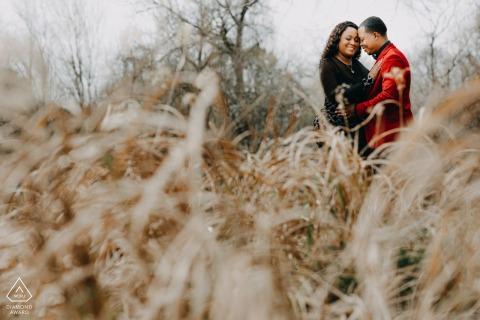 Paar die hun gelukkig ogenblik hebben onder een zonsondergang en lange grassen bij Oyster Creek Park in Sugarland TX