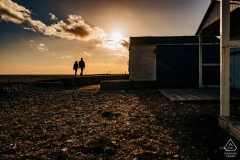 Shoreham Beach, West Sussex, UK pre-wedding image - Couple walking along beach huts at sunset