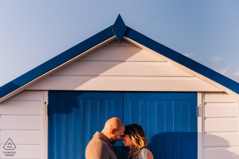 Shoreham Beach, West Sussex, UK Pictures - Close up of couple embracing, framed by a beach hut