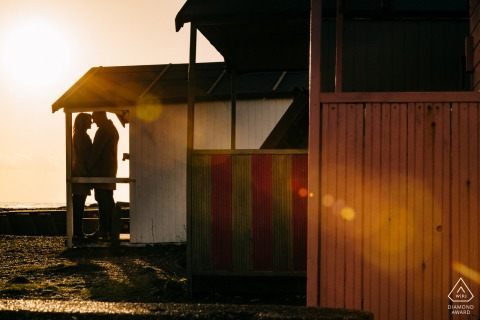 Shoreham Beach, West Sussex, UK - Couple in silhouette framed by beach huts with sunflare