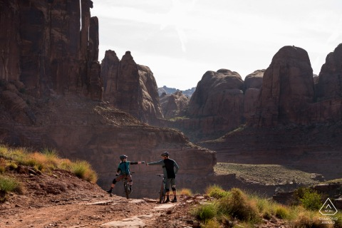 Moab, UT Couple fist bumping after mountain biking during engagement image shoot.