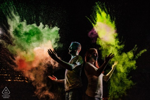 Engaged Couples Photographer | Couple's Back Yard, Falls Church, VA - Couple back to back, throwing holi powder up, side lit to catch the spray!
