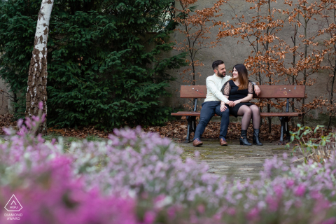 Engagement Photos | Metz, France - Couple is sitting on a bench with purple flowers in first plan