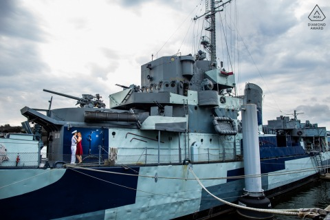 Engaged Couples Photographer | USS Slater, Albany, New York, USA - A military couple cuddles up on board a battleship for their dramatic engagement photo.