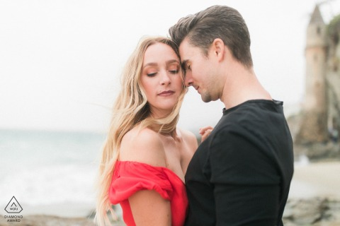 Engagement Photos | Pirate Tower, Laguna Beach, California, USA 	Couple embracing under the rain in front of the Pacific Ocean in California during an engagement session